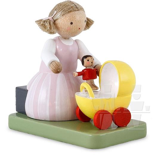 Mädchen sitzend mit Puppe und Puppenwagen