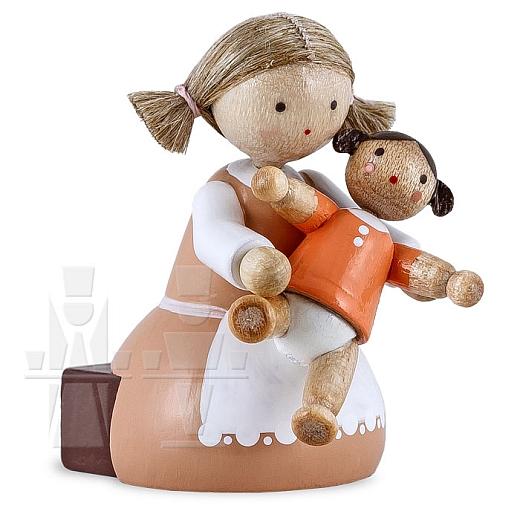 Mädchen sitzend mit Puppe