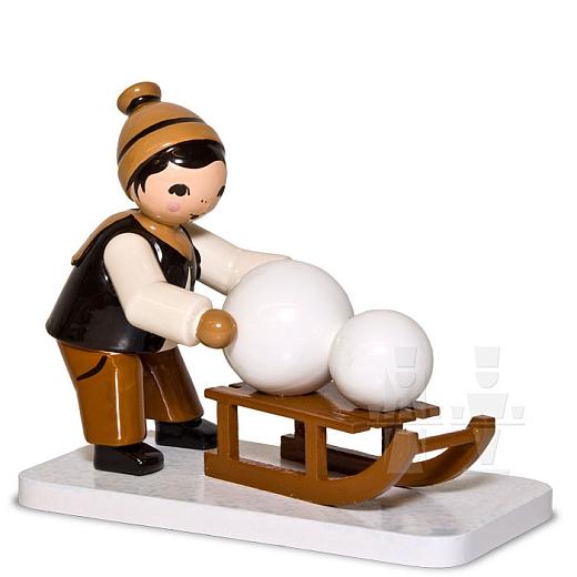 Junge mit Schlitten und Schneekugel braun