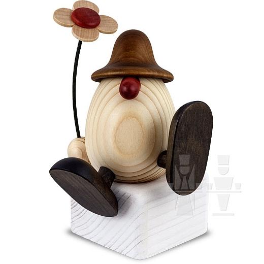 Eierkopf Alfons mit Blume auf Kante sitzend oder tanzend braun