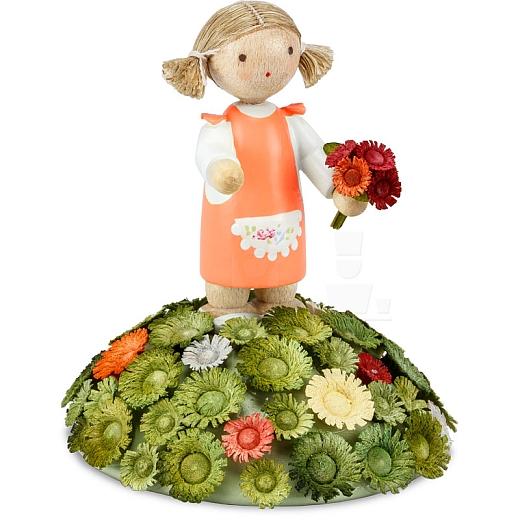Mädchen mit Kleid orange und Blumenstrauß auf Blumenhügel