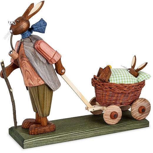 Osterhasengroßvater mit Hasenbaby mit grüner Decke im Wagen