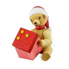 Weihnachtsbär mit Geschenk sitzend