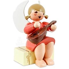 Engel sitzend auf Geschenkpaket mit Mandoline rot