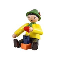 Junge sitzend mit Bausteinen