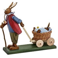 Osterhasengroßvater mit Hasenbaby mit blauer Decke im Wagen