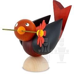Bird colored red with flower in beak wings black