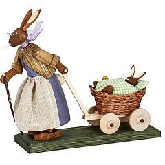 Osterhasengroßmutter mit Hasenbaby im Wagen mit grüner Decke