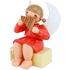 Engel sitzend auf Geschenkpaket mit Panflöte rot