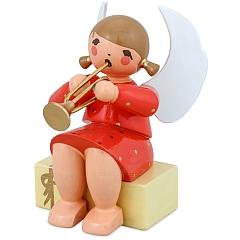 Engel sitzend auf Geschenkpaket mit Trompete rot